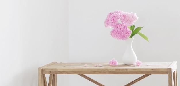 Różowa hortensja w białym wazonie na drewnianej półce na białej ścianie w tle