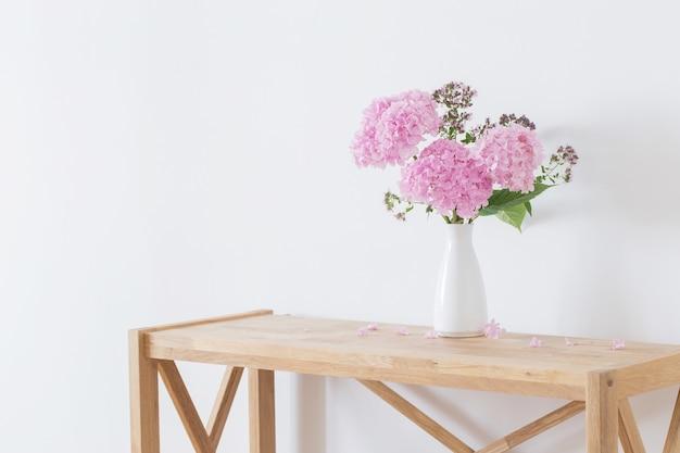 Różowa hortensja w białym wazonie na drewnianej półce na tle białej ściany