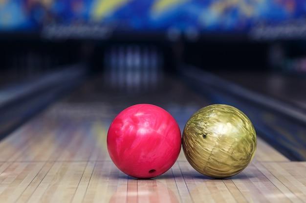 Różowa i żółta piłka na kręgielni przed trafieniem.