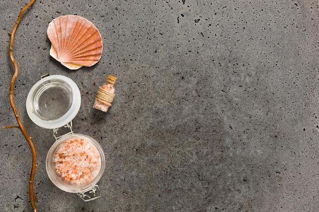 Różowa kąpielowa sól w zbiorniku z seashell na betonie textured