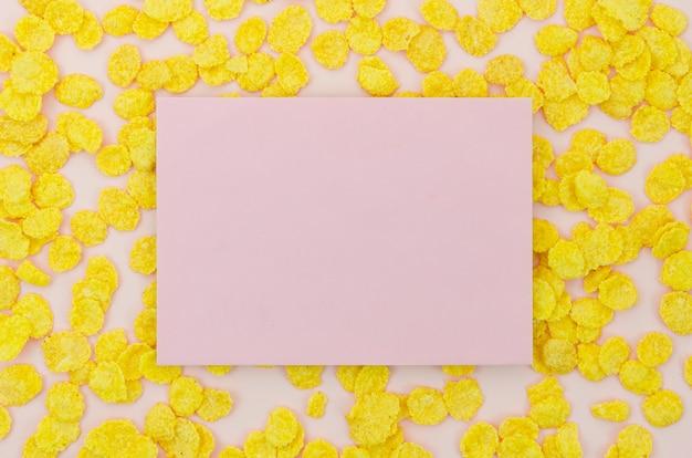 Różowa karta otoczona płatkami kukurydzy