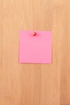 Różowa karteczka przypięta do drewnianej tablicy ogłoszeń