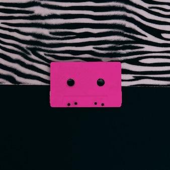 Różowa kaseta audio na nadruku zwierzęcej zebry. minimalna płaska sztuka świecka