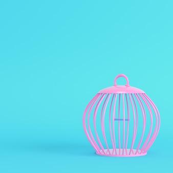 Różowa klatka dla ptaków na jasnoniebieskim tle w pastelowych kolorach
