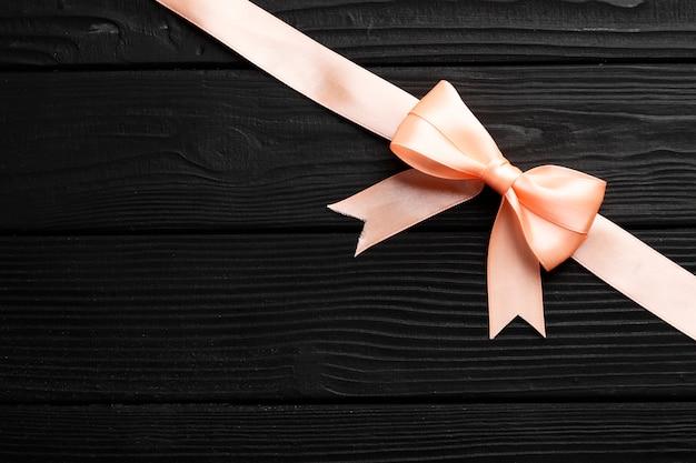 Różowa kokardka i wstążka na drewnianym tle
