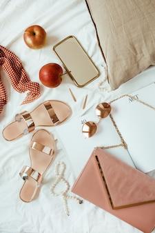 Różowa kompozycja mody damskiej z kobiecymi dodatkami, biżuterią, dodatkami na białej pościeli w łóżku