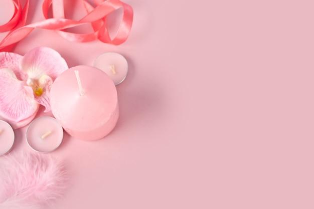 Różowa kompozycja spa ze świecami. aromaterapia, pielęgnacja zdrowia i urody, koncepcja luksusowego kurortu spa. widok z góry. skopiuj miejsce.