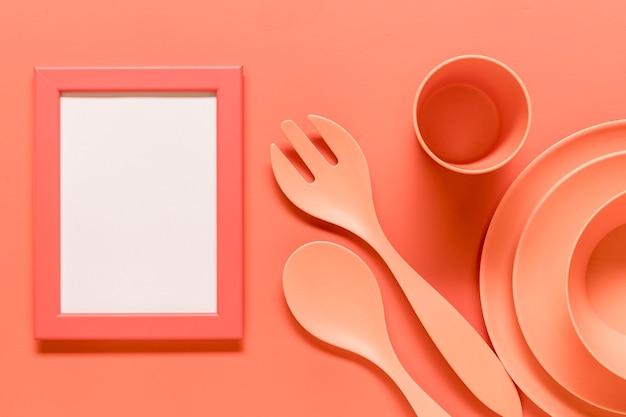 Różowa kompozycja z pustą ramką i plastikowymi naczyniami