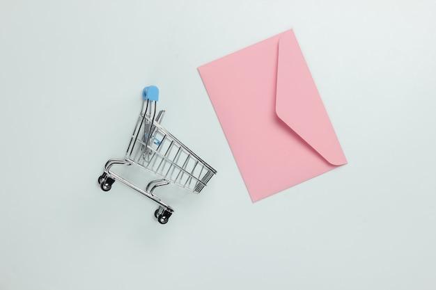 Różowa koperta i wózek na zakupy na białym tle. makieta na walentynki, wesele lub urodziny. widok z góry