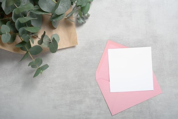 Różowa koperta kwadratowa karta z zaproszeniem, makieta z życzeniami z bukietem eukaliptusa.