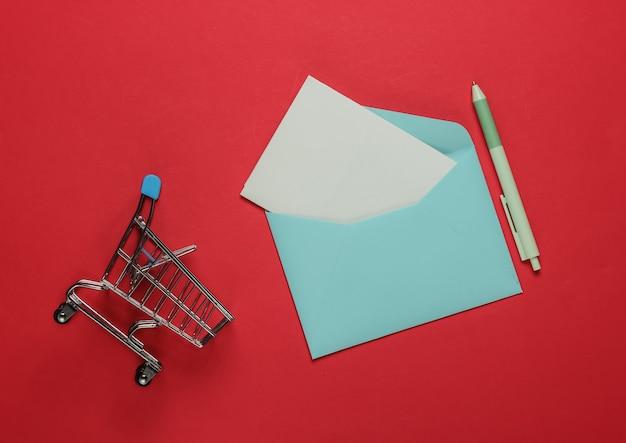 Różowa koperta z listem i wózkiem na zakupy na czerwonym tle. makieta na walentynki, wesele lub urodziny. widok z góry