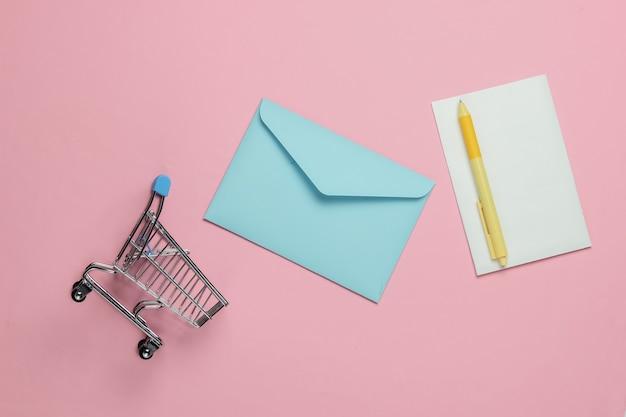 Różowa koperta z listem i wózkiem na zakupy na różowym pastelowym tle. makieta na walentynki, wesele lub urodziny. widok z góry