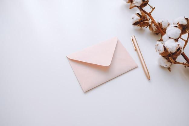 Różowa koperta z piórem na białym tle, z gałązką bawełny