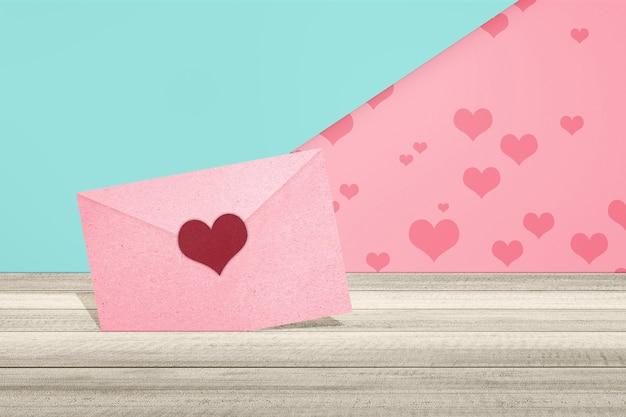 Różowa koperta z sercem na stole z kolorowym tłem. walentynki