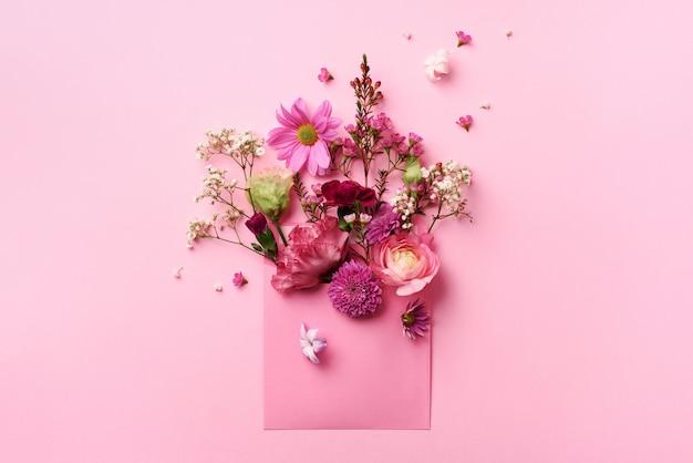 Różowa koperta z wiosennymi kwiatami.