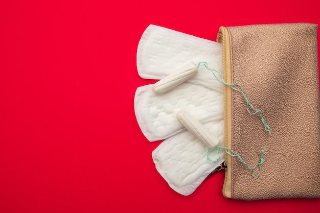 Różowa kosmetyczka z bawełnianymi podpaskami i tamponami do codziennej higieny.