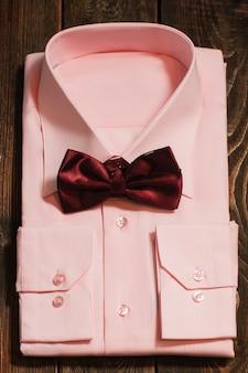 Różowa koszula męska z satynową muszką na drewnianym biurku
