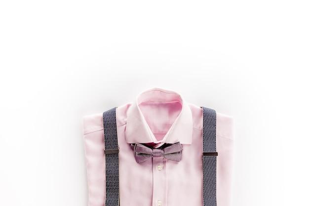 Różowa koszula z muszką i szelkami na białym tle
