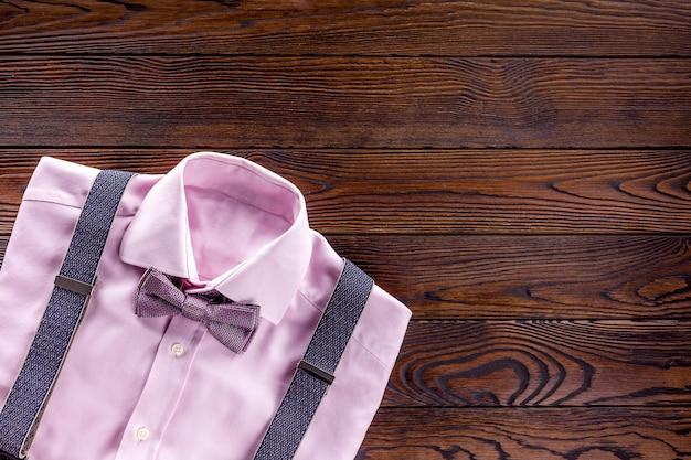 Różowa koszula z muszką i szelkami na ciemnym drewnie