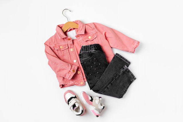 Różowa kurtka na wieszaku i jeansy z trampkami. zestaw ubrań i akcesoriów dla dzieci na wiosnę, jesień lub lato na białym tle. moda dla dzieci strój. płaski układanie, widok z góry