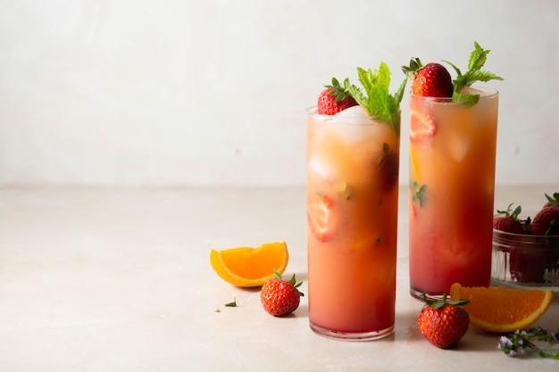 Różowa lemoniada ze świeżymi truskawkami, owocami pomarańczy i miętą. świeże letnie koktajle owocowe.