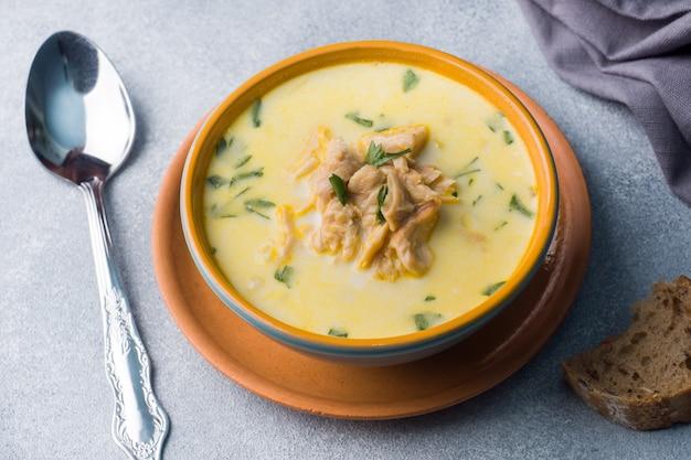 Różowa łosoś zupa rybna ze śmietaną w ceramicznej misce.