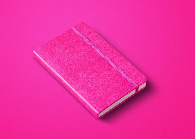 Różowa makieta zamkniętego notebooka na białym tle na kolorowym tle
