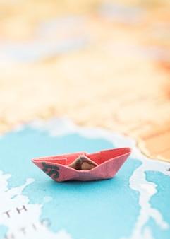 Różowa mała łódka na mapie świata