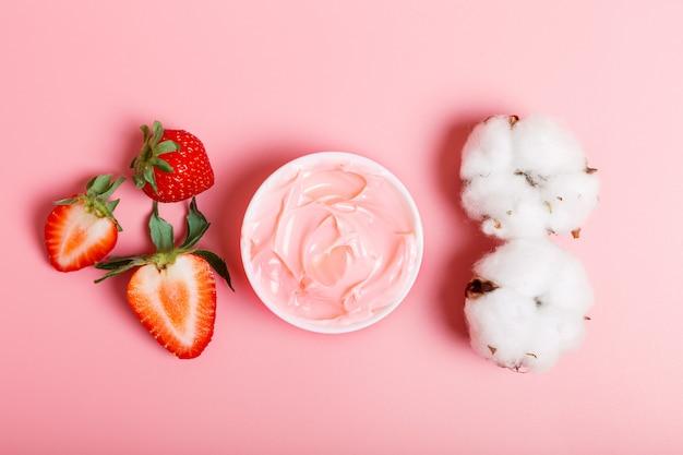 Różowa maska kremowa lub na twarz, świeże dojrzałe truskawki i bawełna na różowym tle. pojęcie kosmetyków naturalnych. pojęcie piękna. leżał płasko, zbliżenie.
