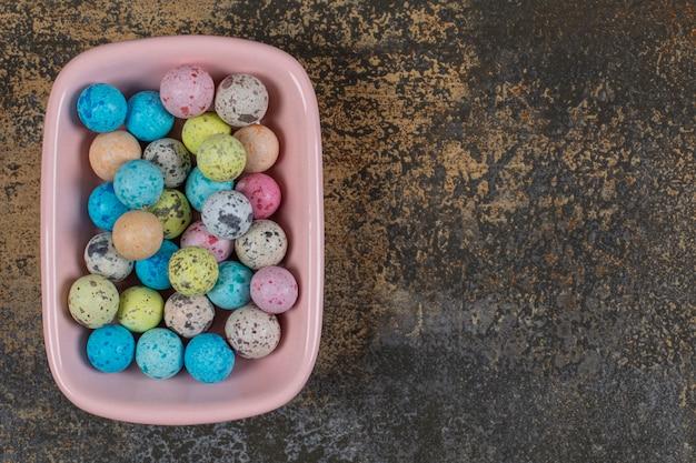 Różowa miska kolorowych cukierków na marmurze.