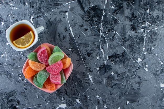 Różowa miska kolorowych marmolad z filiżanką gorącej herbaty na marmurowej powierzchni.