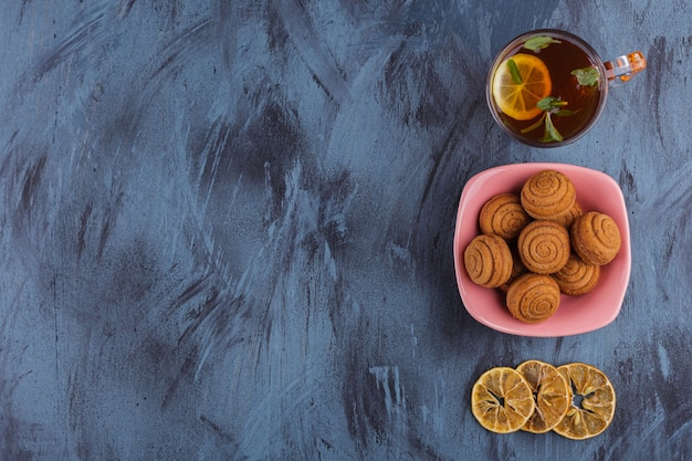 Różowa miska mini ciastek cynamonowych ze szklanką herbaty na kamieniu.