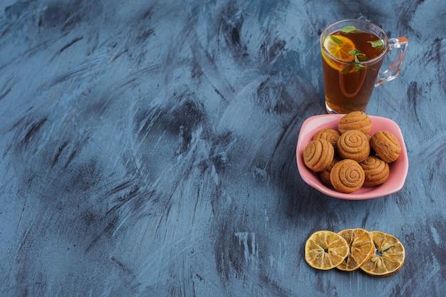 Różowa miska mini ciastek cynamonowych ze szklanką herbaty na kamiennym tle.