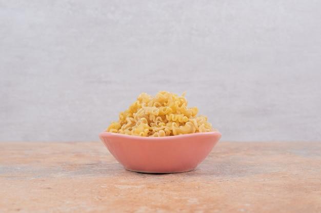 Różowa miska nieprzygotowanego makaronu na marmurowym tle. wysokiej jakości zdjęcie