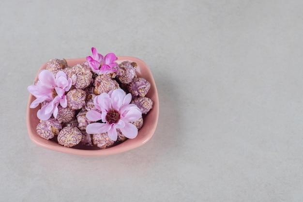 Różowa miska pełna smakowego popcornu ozdobiona kwiatami na marmurowym stole.