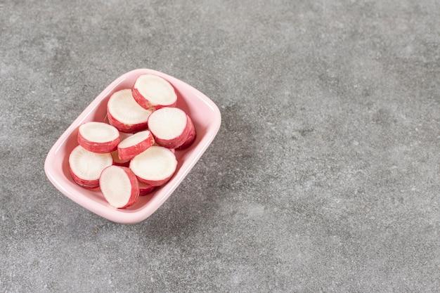 Różowa miska pokrojonej w plasterki czerwonej rzodkwi na powierzchni marmuru.