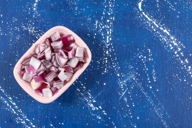 Różowa miska pokrojonej w plastry fioletowej cebuli na marmurowym stole.