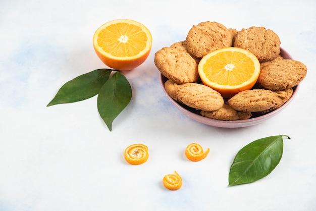 Różowa miska wypełniona domowymi ciasteczkami i na pół pokrojoną pomarańczą z liśćmi na białej powierzchni.