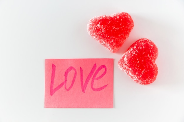Różowa naklejka z napisem love i dwiema czerwonymi marmoladami w kształcie serca. symbol miłości na białym tle