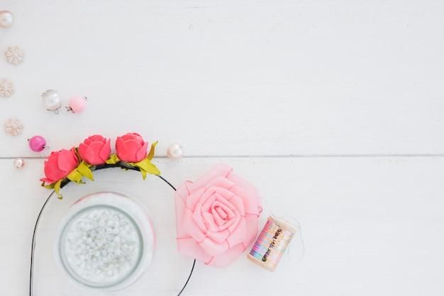 Różowa opaska do włosów; sieczka; szpula srebrna i różowa róża ze wstążką na drewnianym tle