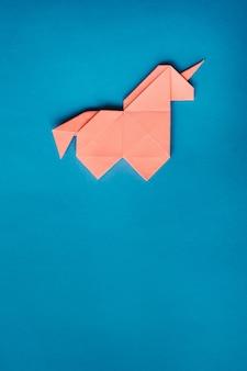 Różowa origami jednorożec na niebieskim tle