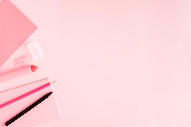 Różowa papeteria na kolorowej powierzchni