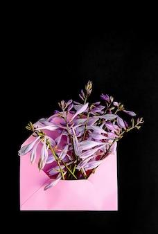 Różowa papierowa koperta ze świeżymi kwiatami ogrodowymi na jasnoniebieskim tle. świąteczny kwiatowy szablon. projekt karty z pozdrowieniami. widok z góry. ujęcie pionowe.