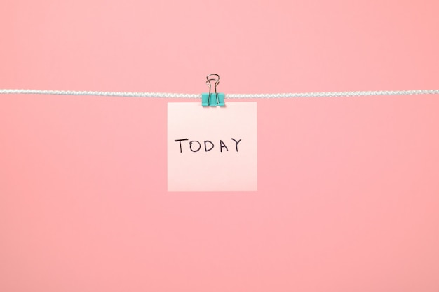 Różowa papierowa notatka wisząca na sznurku z tekstem today
