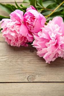 Różowa peonia kwitnie na szarym drewnianym tle.