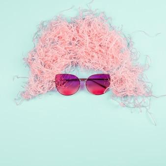 Różowa peruka z rozdrobnionego papieru i okulary na tle mięty