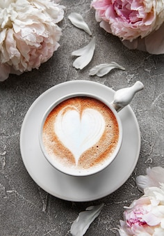 Różowa piwonia i filiżanka kawy w pięknym stylu na szarym tle betonu. tle kwiatów. widok z góry.