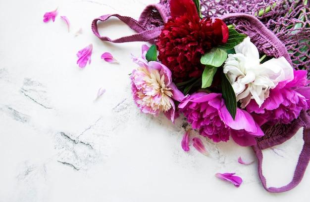 Różowa piwonia w woreczku ze sznurka na powierzchni białego marmuru
