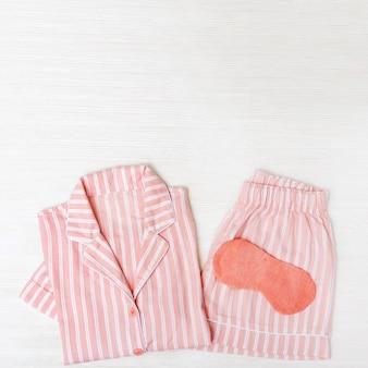 Różowa piżama dla dziewczynki, maska do spania na białym drewnie.