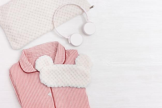 Różowa piżama dla dziewczynki, maska na oczy do spania, słuchawki, miękka poduszka na białym drewnie.